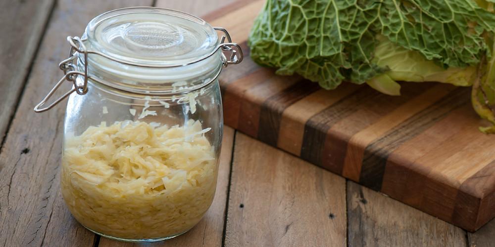 Jar of sauerkraut next to cabbage