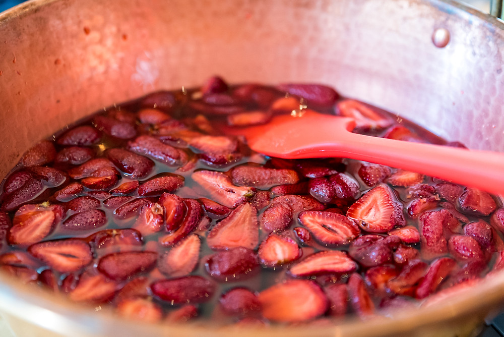 Gleaming copper jam pan with strawberries