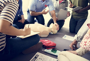 An instructor operating on a CPR mannequin, teaching a class of non-medical students CPR and AED as they take notes.