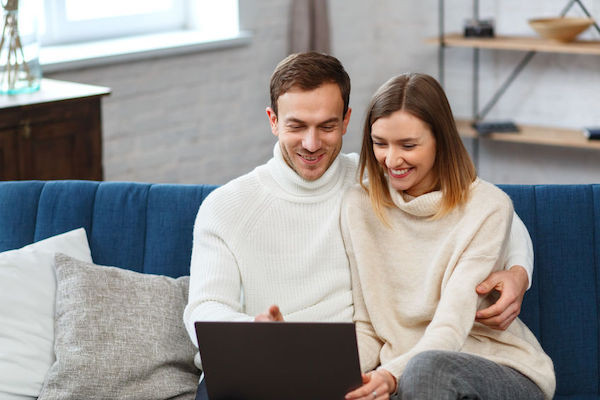 Young couple watching a live stream of a friends wedding ceremony