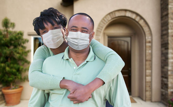 young engaged couple wearing masks to protect from COVID-19