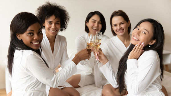 A bride and some friends wearing bathrobes and drinking champagne at a bachelorette party in an Airbnb
