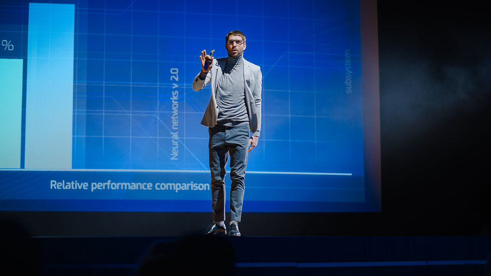 Successful Male Speaker Stands on Stage,