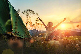 Happy woman with open arms stay near tent around mountains under sunset light sky enjoying