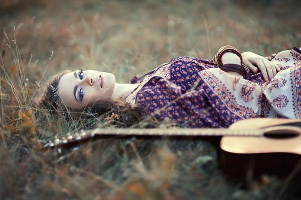 Beautiful hippie girl with guitar lying