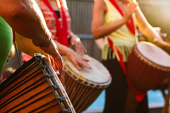 Close-up of people's hands playing on African djembe drums on a sunny summer evening..jpg