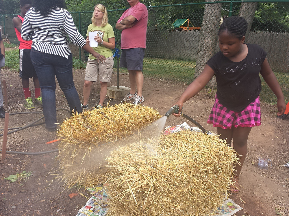 A young girl water a straw bale during a gardening workshop at the Pottstown Community Garden. The bales take 12 days to condition for planting which include watering and fertilizing daily.
