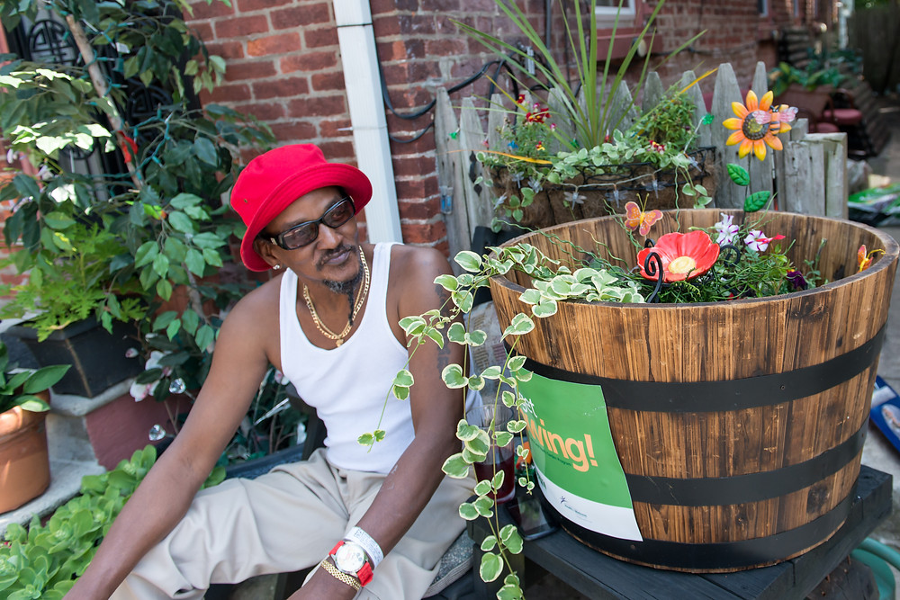 Larry Wyatt sits in front of his Chestnut Street home garden which was entered in the 2015 Pottstown Home Garden Contest.