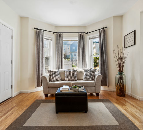 Living Room with tan couch and large windows behind it
