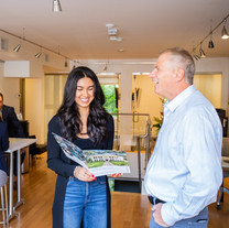 Agent Brianna Ayube and Broker/Owner talk about marketing while the Kerry Dowlin team meets with Broker/Owner Steve Chuha in the background