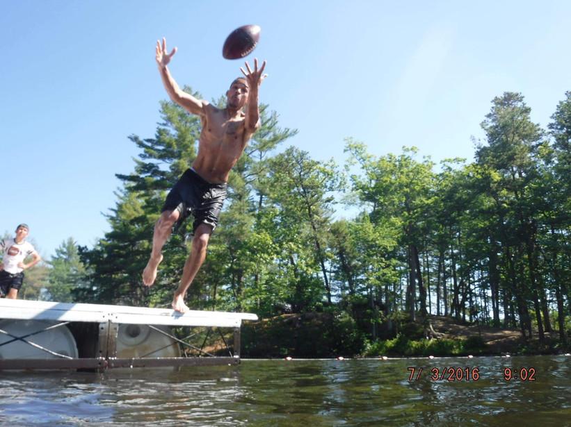 Jamie playing football at the lake