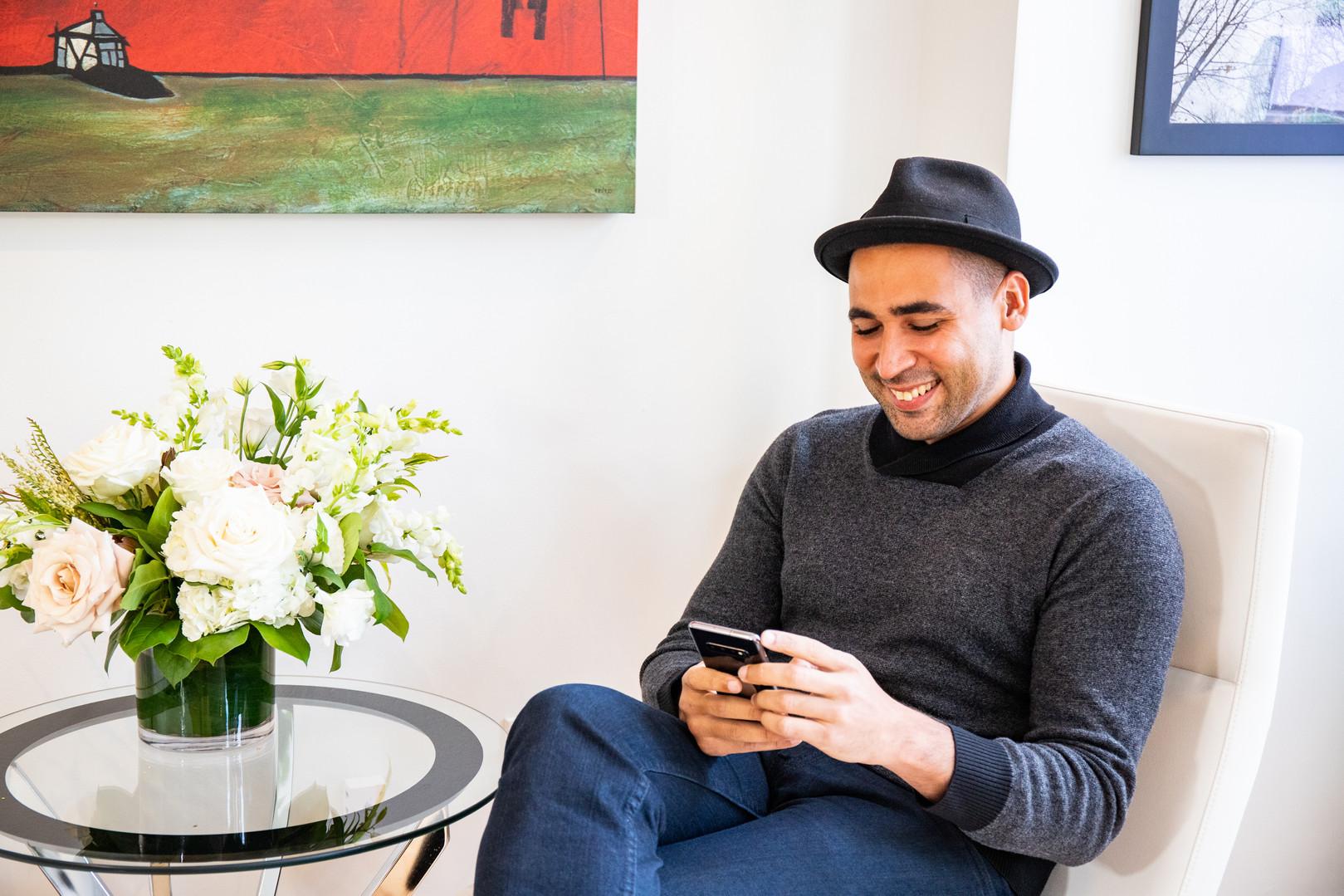 Agente, Julio Torres-Santana revisa sus correos electrónicos en su teléfono en nuestra oficina de Boston
