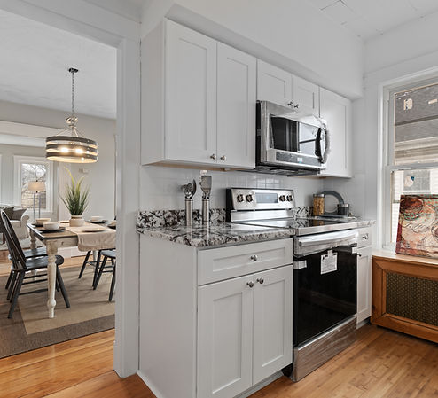 Small kitchen with white cabinets and granite countertops peeking into dining room