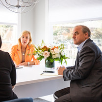 Agents Sharon Coskren and Ray Durling talking in the Andover office