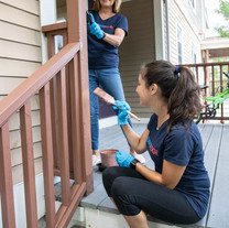 Staff members Amanda and Mary Ellen paint homes during a volunteer day with Housing Families
