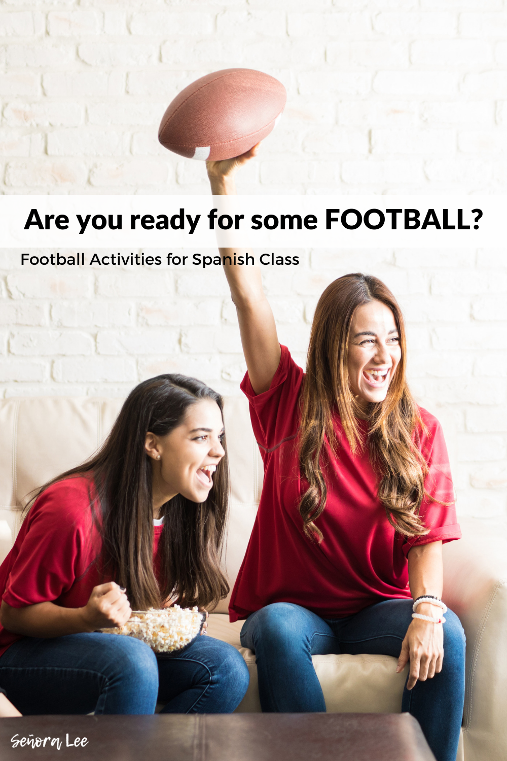 two girls watching a football game with football in hand