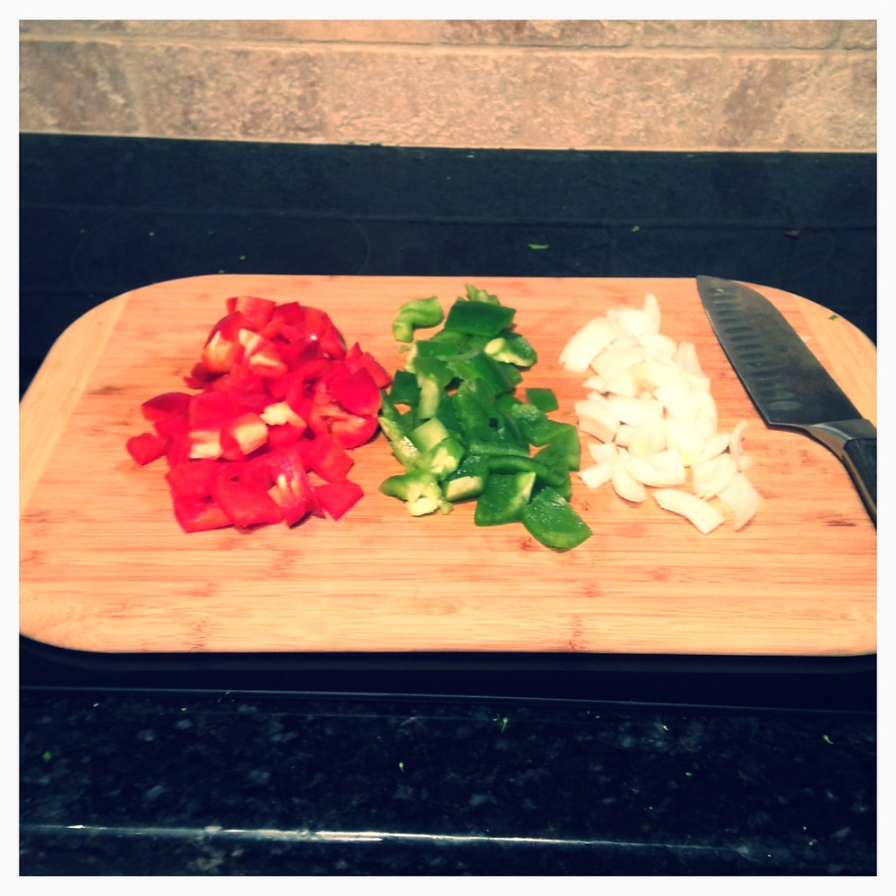 Chopped Bell Peppers and onions on cutting board