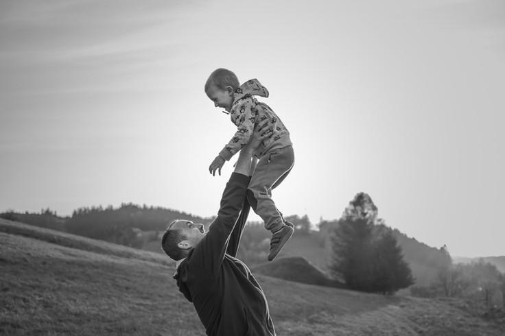 Otec zvedá syna do vzduchu v přírodě