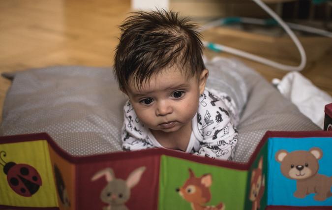 Fotka novorozence, který si prohlíží obrázkovou knihu