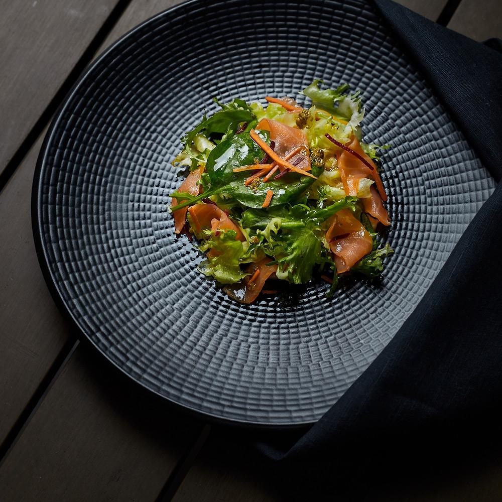 Pretty salad visually pops on a dark plate