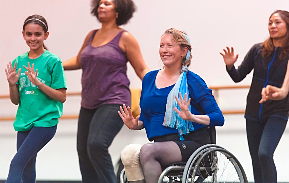 Four smiling female dancers of diverse ages and races.