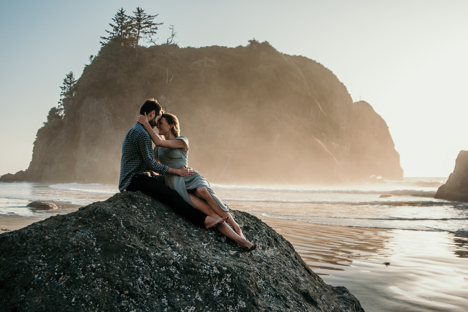 A couple sits on a rock in front of a sea stack on Ruby Beach in Washington