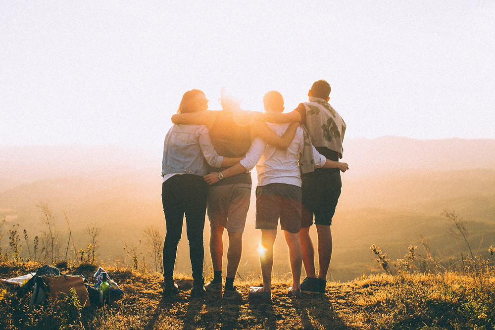 Four adults with arms around each other looking at the sunset connecting with each other to relieve stress in Denver CO. We provide counseling for stress management treatment in Englewood CO with Catalyss Counseling 80209 and 80210