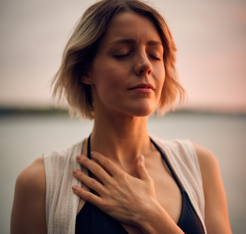 women breathing and meditating with her hand on her heart