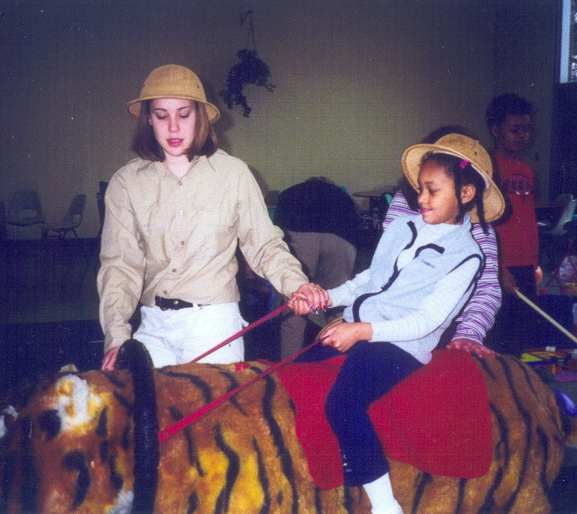 A young girl is riding a large stuffed tiger, guided by a woman dressed in a safari outfit.