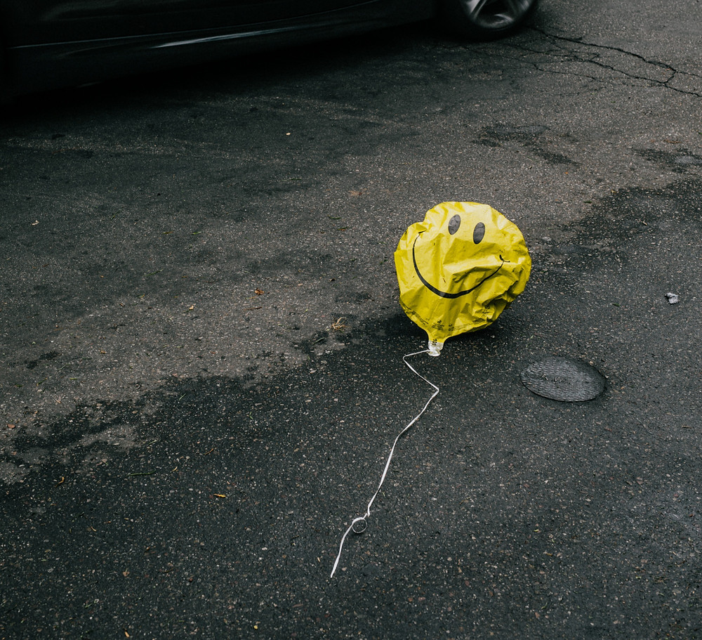 a popped yellow happy face baloon showing sadness and depression