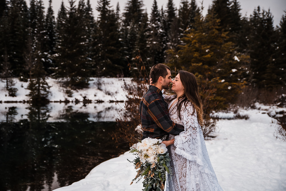 A couple hugs during their snowy elopement day at Gold Creek Pond in Washington