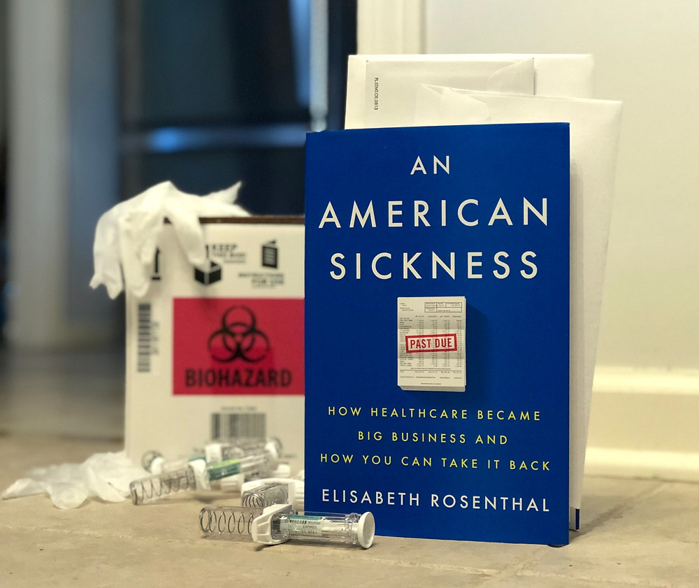 The book An American Sickness is in the foreground with biohazard materials in the background