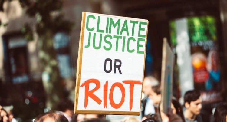 Person holding up a sign supporting climate justice