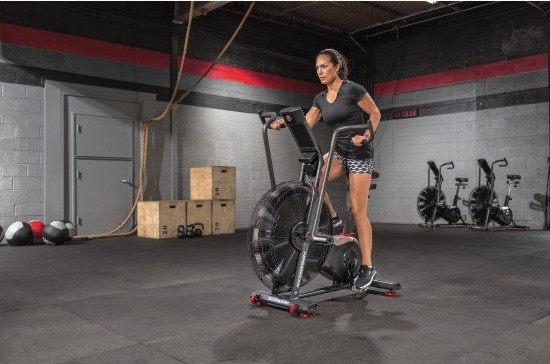 woman exercising on an airdyne bike in a cross-fit gym