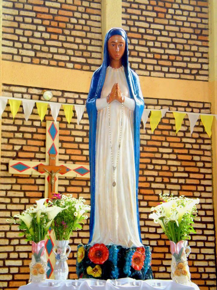 Nossa Senhora das 7 dores de Kibeho se apresenta de pe com as mãos justapostas em oração, túnica branca, véu azul cobalto que vai até os pés. Cor da pele mestiça parda. ao fundo parede de tijolinho aparente do Santuário, um belo crucifixo bandeirolas amarelo e branco, flores.