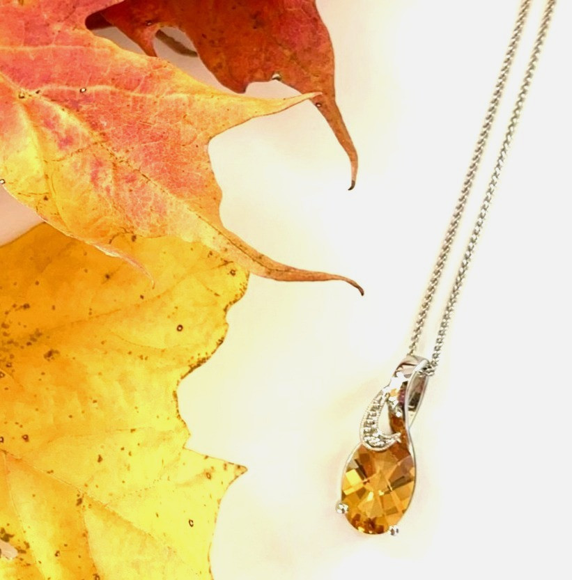 oval yellow orange citrine white gold pendant with diamonds on chain on white background next to dry maple leaves