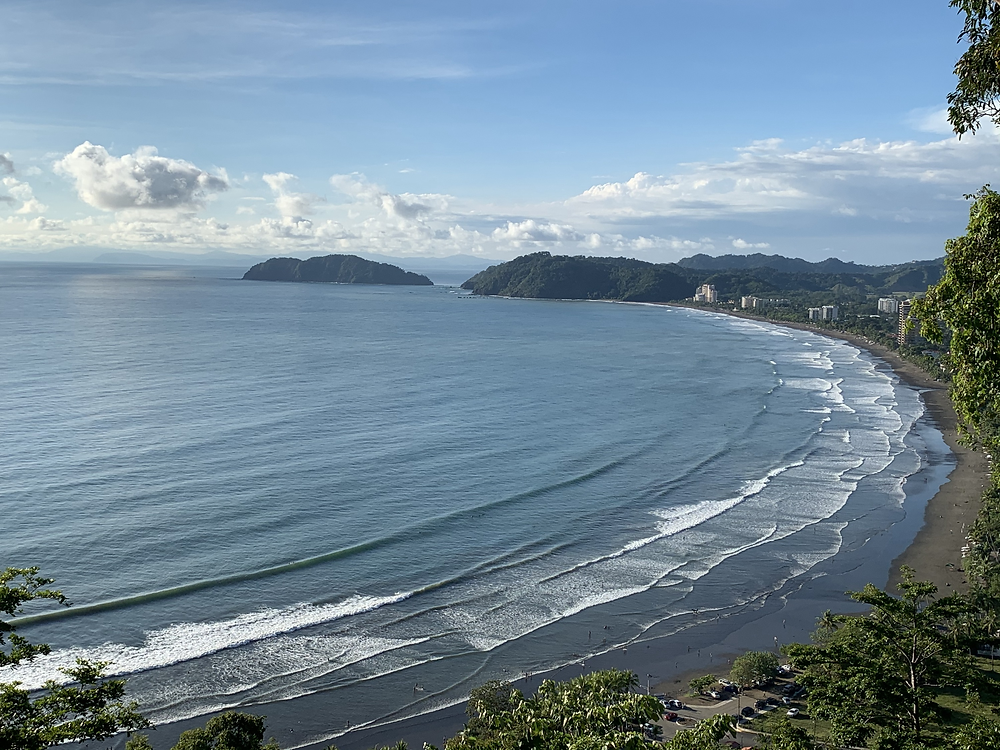 View looking down at Jaco beach from an outlook. Waves crash near the shoreline. It is a blue sky day with a few white clouds.