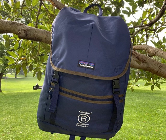 A Patagonia backpack with a B Corp logo hanging on a tree.