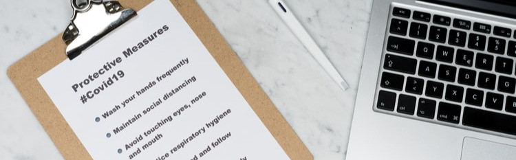 Paper on a clipboard next to a laptop, placed on a white table