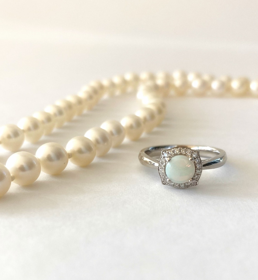 pearl necklace next to round opal vintage inspired white gold engagement ring on a white background
