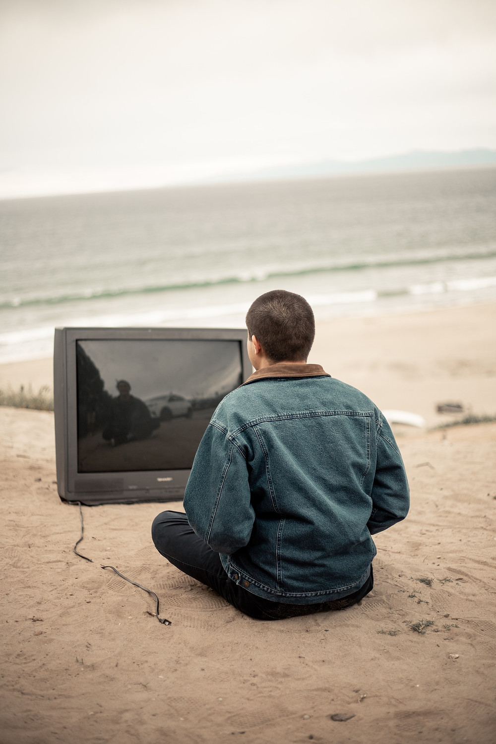 Man sitting on a beach in front of an unplugged TV limiting his media exposure during coronavirus to help manage his anxiety in Englewood CO. We can help with anxiety treatment and therapy at Catalyss Counseling in Denver CO 80209 and 80210