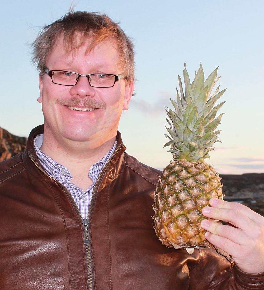 Hans Olav Brendberg holder smilende en ananas, med horisonten i bakgrunnen