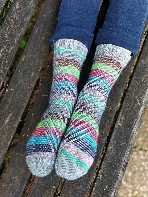 Hand-knit socks with a swirling multi-colored pattern