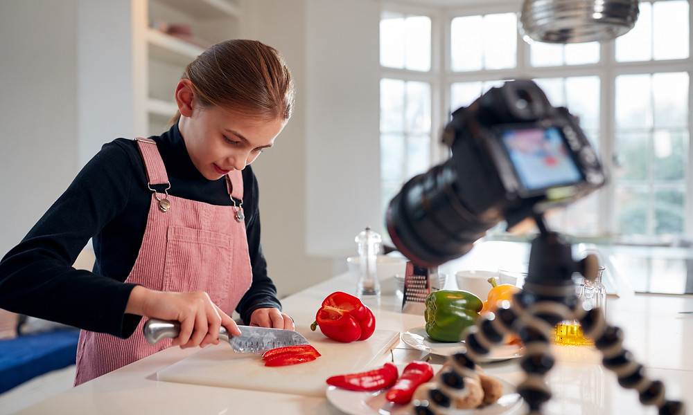 Teenage girl filming herself cooking: online blog: The Parents' Guide to