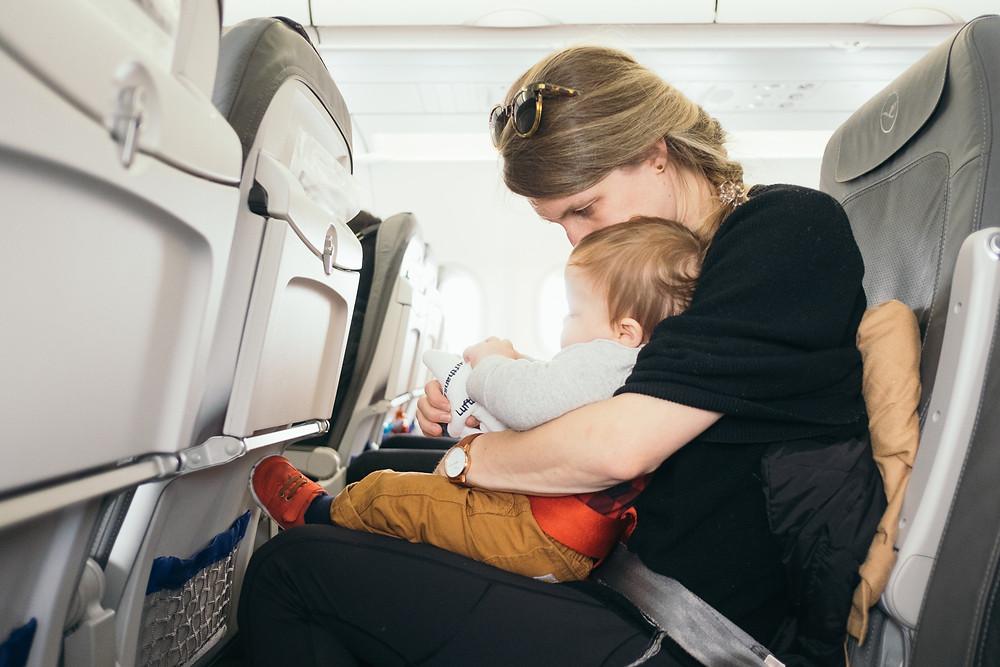 Mujer carga en brazos a bebé a bordo de un avión