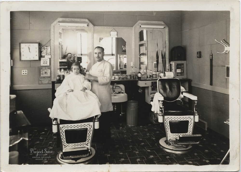 Men's barber Zeroon Malkasian poses with his daughter Diana after cutting her hair,  1032 Chicago Ave, Evanston, Illinois, 1941; photographer, seen in mirror, unknown.  Up to this time, Diana had rag curls and remembers that this short cut was easier to take care of.  Courtesy of Diana Malkasian Eggleston