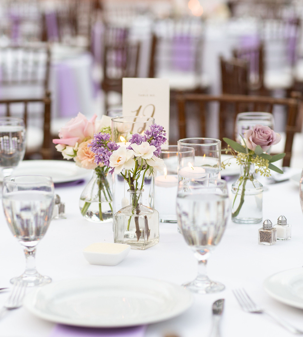 Sweet and simple centerpieces with bud vases and floating candles  for a purple wedding, filled with eucalyptus, sweet peas, carnations, ranunculus, lilac, spray roses, and amnesia roses that perfectly matched their purple and mauve color palette  for a stunning wedding at Rancho Las Lomas in Orange County, CA made by San Diego wedding florist Le Champange Projects