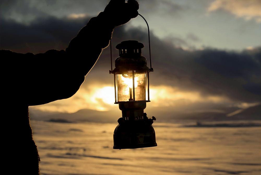 Lit lantern at sunset beach scene