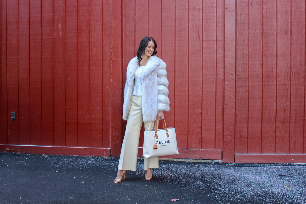 Woman in Winter White Jacket with cream pants and a white celine tote bag