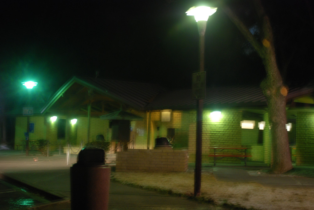 A night scene of a building with a few lights and a tall parking lot light is in the foreground of the image.